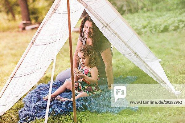 Reife Frau und Enkelin sitzen im hausgemachten Gartenzelt und essen Kekse.