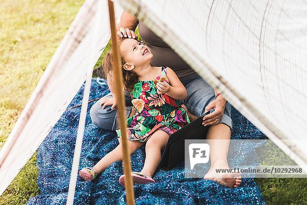 Mature woman and granddaughter sitting in homemade garden tent using digital tablet