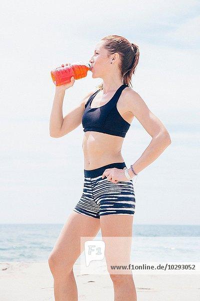 Mittlere erwachsene Frau  die am Strand steht und aus einer Plastikflasche trinkt.