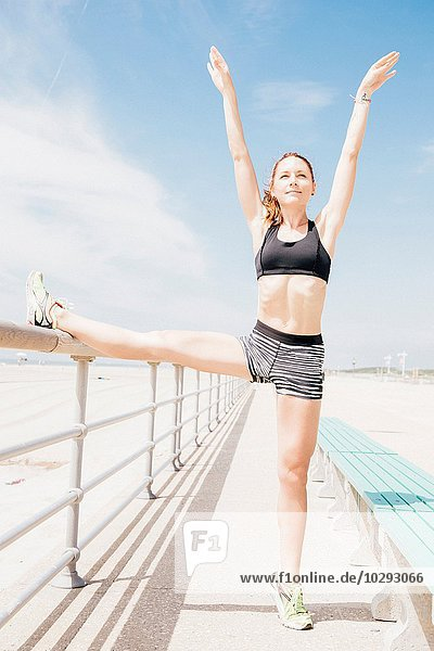 Mittlere erwachsene Frau steht am Strand und streckt sich gegen Geländer.