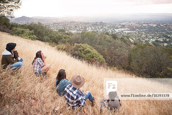 Junger Mann und vier erwachsene Schwestern  die vom grasbewachsenen Hügel hinausblicken.