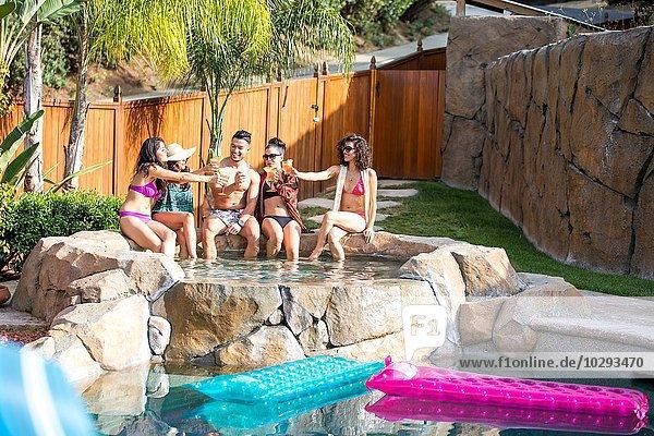 Junger Mann und vier Schwestern stoßen mit Cocktails im Garten an.