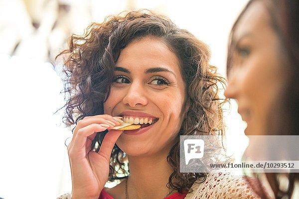 Junge Frau und Schwester beim Snacken von Käse und Keksen