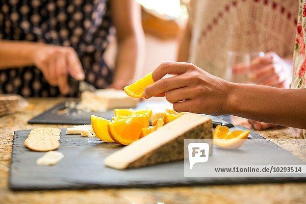 Nahaufnahme von drei erwachsenen Schwestern beim Snacken vom Käsebrett