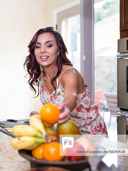 Mittlere erwachsene Frau  die Orange aus der Obstschale holt