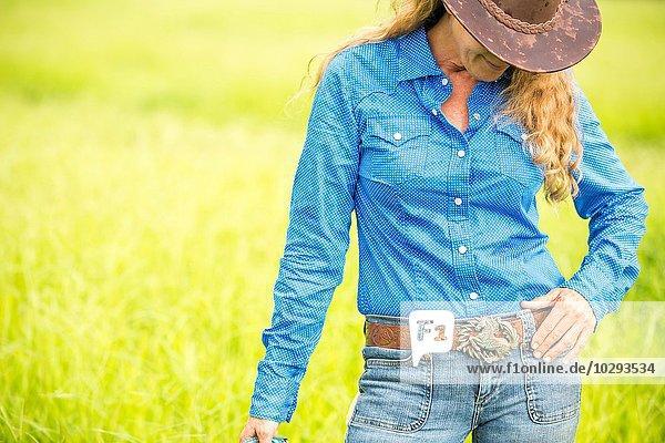 Porträt einer reifen Frau  im Feld stehend  mit Jeans und Cowboyhut.