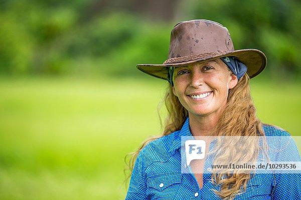 Porträt einer reifen Frau  im Feld stehend  mit Jeanshemd und Cowboyhut