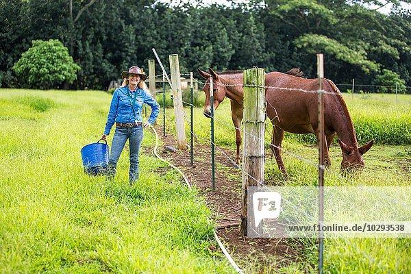 Porträt einer reifen Frau  im Feld  neben dem Pferd stehend
