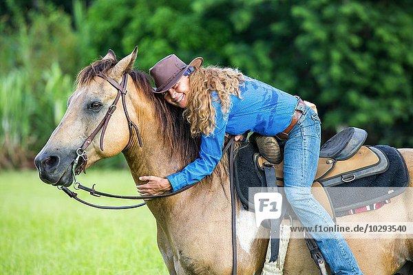 Porträt einer reifen Frau  zu Pferd  umarmendes Pferd
