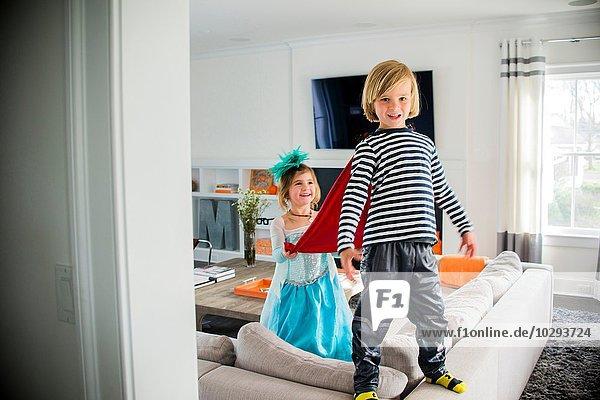 Kinder in Kostümen spielen auf dem Sofa
