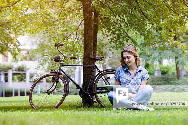 Junge Frau sitzend auf Gras neben dem Fahrrad mit digitalem Tablett