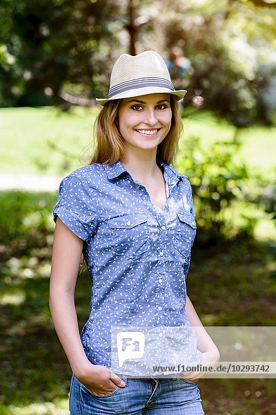 Portrait of young woman wearing panama hat  hands in pockets  looking at camera smiling