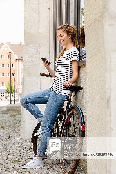 Seitenansicht der jungen Frau  die das Fahrrad an der Gebäudeaußenseite anlehnt und das Smartphone lächelnd betrachtet.