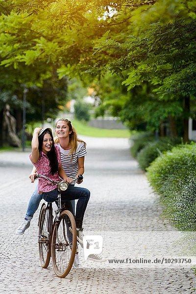 Vorderansicht von jungen Frauen  die sich eine Fahrradtour teilen und sich am Hut festhalten.