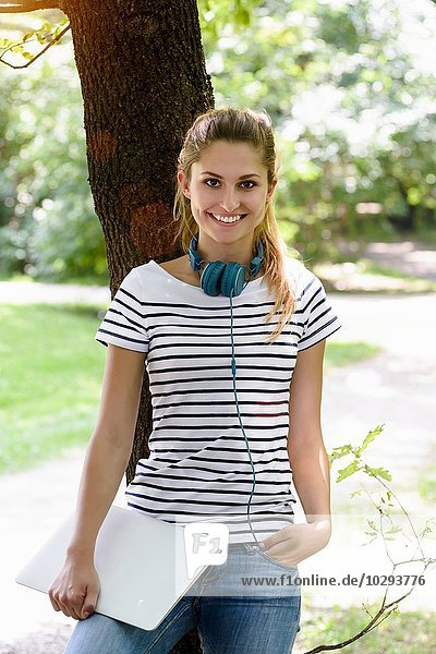 Young woman with headphones leaning against tree  hand in pocket  holding laptop looking at camera smiling