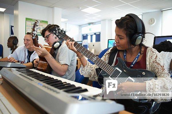 Kleine Gruppe von Studenten  die vor Keyboards sitzen und Kopfhörer tragen und Gitarren spielen.