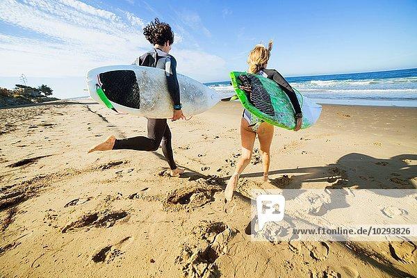 Paar läuft zum Meer  trägt Surfbretter  Rückansicht