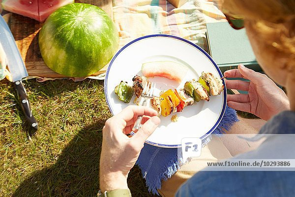 Man with plate of kebab at picnic party