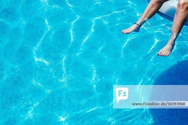 Beine und Füße eines Mädchens  das im Schwimmbad baumelt.