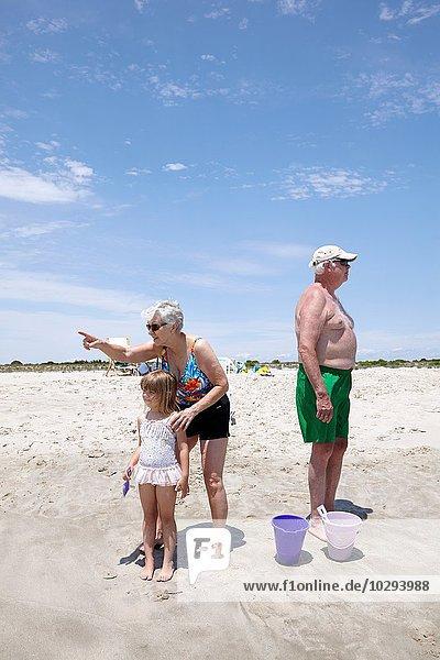 Seniorin mit Enkelin  die auf den Strand zeigt und schaut.
