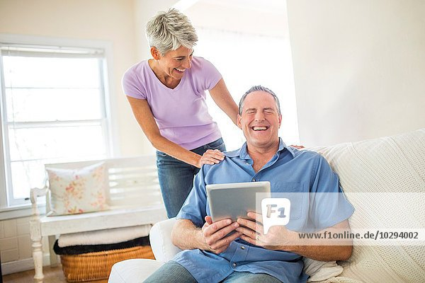 Reife Paare lachen bei der Benutzung des digitalen Tabletts