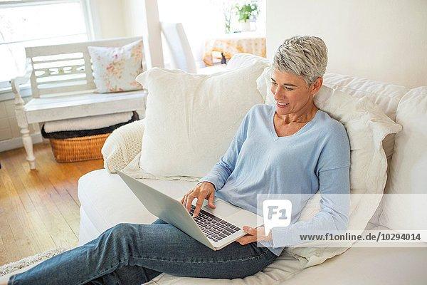 Reife Frau  die auf dem Sofa liegt und auf dem Laptop tippt.