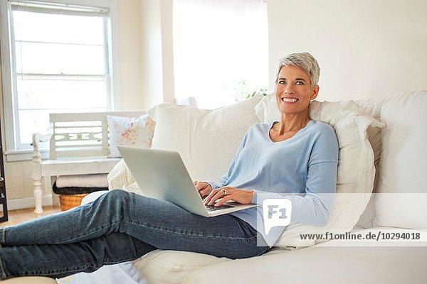 Portrait einer reifen Frau  die auf dem Sofa liegt und auf dem Laptop tippt