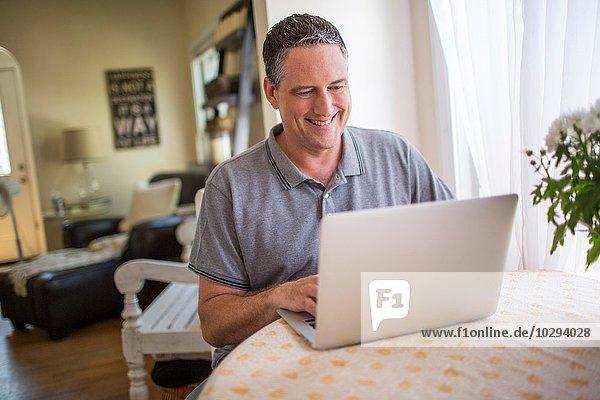 Reifer Mann beim Tippen auf dem Laptop am Küchentisch