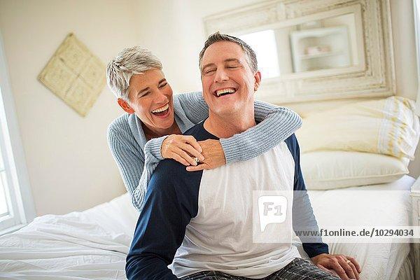 Ein reifes Paar  das auf dem Bett lacht und herumalbert.