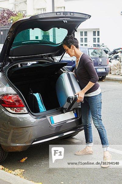 Frau steht neben dem Auto und stellt den Koffer in den offenen Kofferraum.