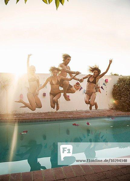 Mittlerer Erwachsener Mann und drei junge Frauen  die auf der Party ins Schwimmbad springen.
