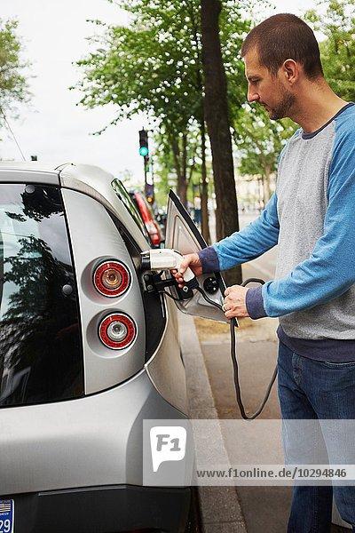 Mann lädt Elektroauto auf der Straße  Paris  Frankreich
