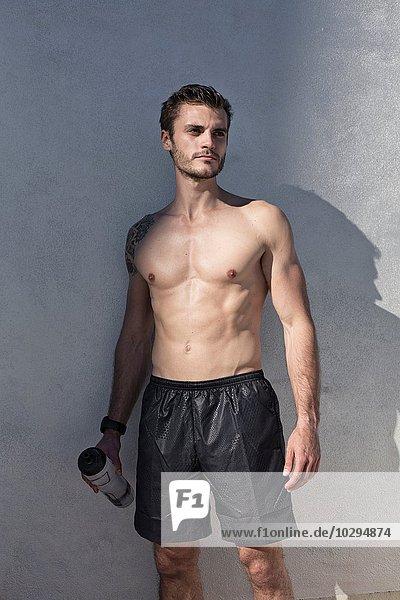 stehend Wasser Mann halten jung nackt Flasche wegsehen