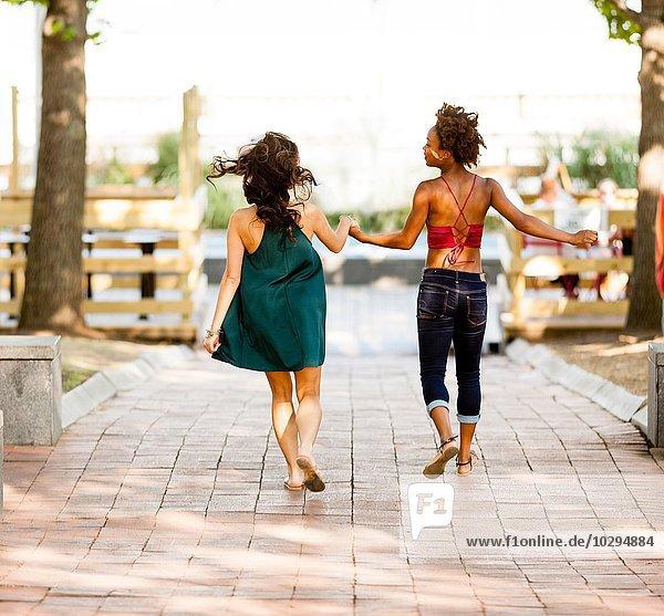 Junge Frauen  die auf der Kopfsteinpflasterstraße laufen.