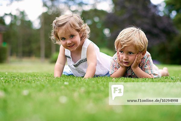 Surface level of boy and girl lying on grass