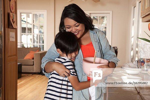 Junge umarmende Mutter in der Küche