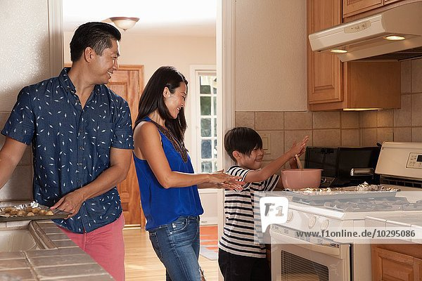Boy and parents preparing food in kitchen