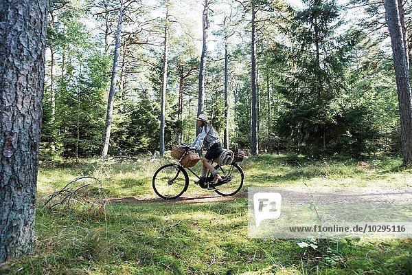 Reife Frau beim Radfahren mit Futterkörben im Wald