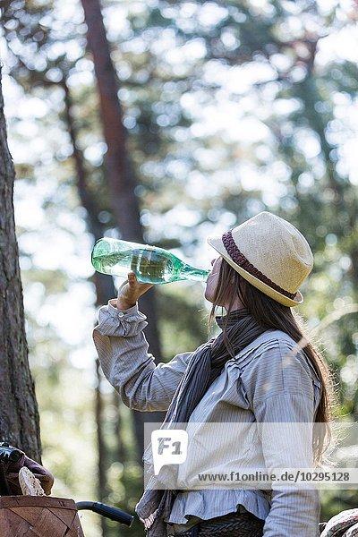 Reife Radfahrerin trinkt aus der Wasserflasche im Wald