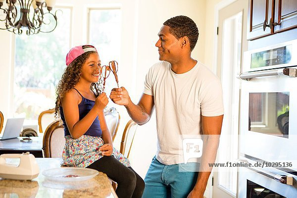 Father and daughter in kitchen making a toast with cake mix covered whisks smiling