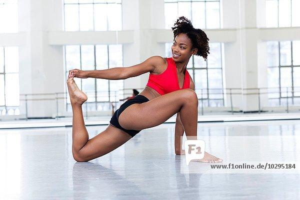 Junge Frau im Tanzstudio streckt das Bein  schaut lächelnd weg