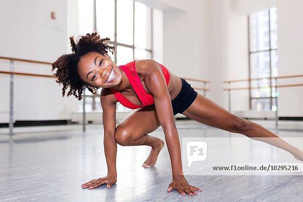 Junge Frau im Tanzstudio auf Händen ruhend  Bein ausgestreckt  Kamera lächelnd anschauend