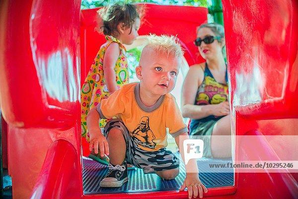 Mutter und Kinder beim Spielen auf der roten Spielplatzrutsche