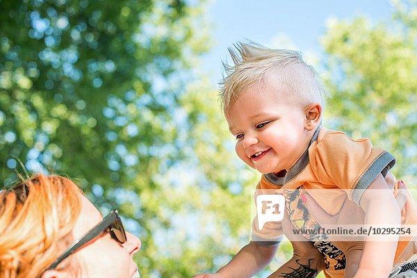 Niedriger Blickwinkel der Mutter  die lächelndes Baby hochhält