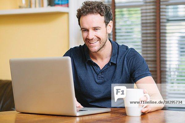 Mittlerer erwachsener Mann  der vor dem Fenster sitzt und lächelndes Laptop benutzt