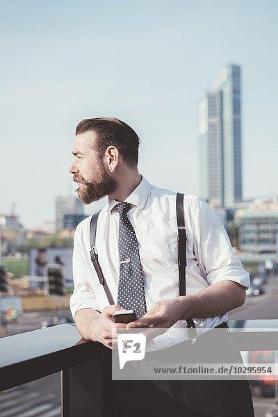 Stilvoller Geschäftsmann mit Blick vom Bürobalkon aus