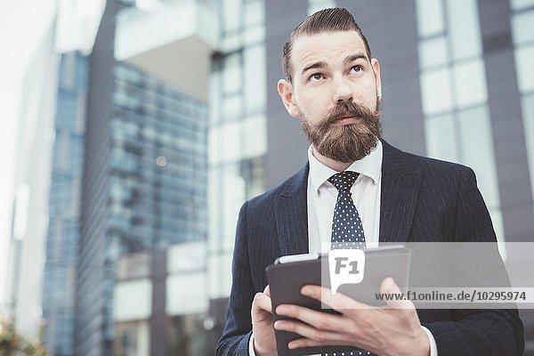 Stilvoller Geschäftsmann mit digitalem Tablett-Touchscreen außerhalb des Büros