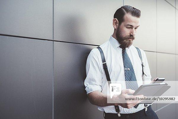 Stilvoller Geschäftsmann mit digitalem Tablett und Smartphone außerhalb des Büros