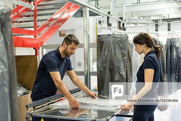 Lagerarbeiter verpacken Bekleidungsbestand in Kunststoff im Auslieferungslager