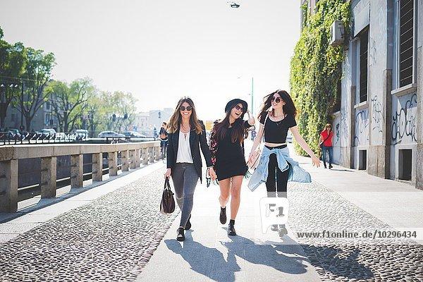 Drei stilvolle junge Freundinnen beim Spaziergang auf dem Bürgersteig
